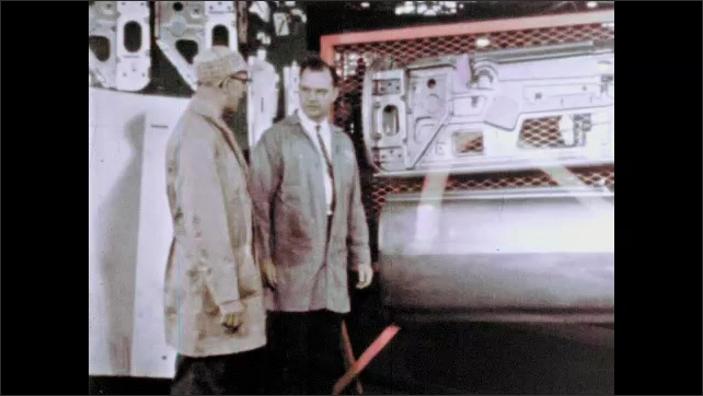 1960s: UNITED STATES: hot metal strips on machine. Men look at machines in factory.