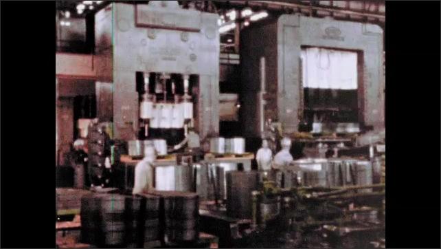 1960s: UNITED STATES: man pushes metal sheet onto conveyor. Man cleans conveyor. Workers in metal factory