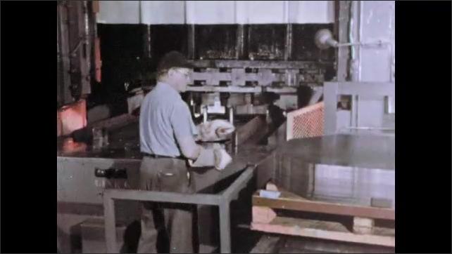 1960s: UNITED STATES: man puts metal sheets on conveyor. Pressing machine