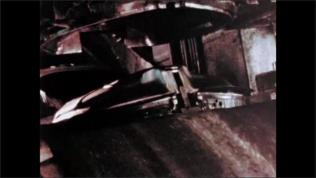 1960s: UNITED STATES: machine shapes metal. Metal pressed by machine. Man feeds metal onto conveyor.