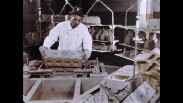 1960s: UNITED STATES: worker removes metal from molds. Man picks up molds.