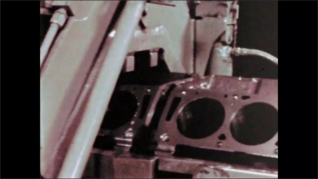 1960s: Machine pumps liquid over engine casing on conveyor belt. Engine casings move on belt then stop as man inspects one.