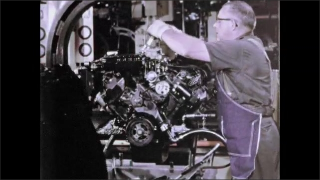 1960s: In factory, man puts parts onto engine block. Man secures part on top of engine block.