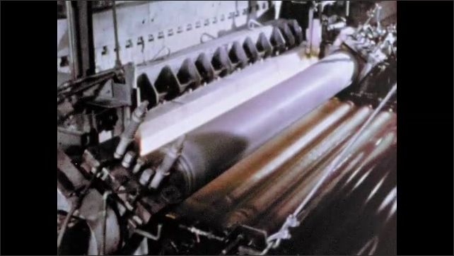 1960s: Rollers turn on large machine in factory. Rollers turn on conveyor belt.