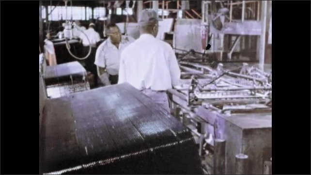 1960s: Two men in factory pick up large sheet of glass from stack and place it on conveyor belt and fasten it into carriage.