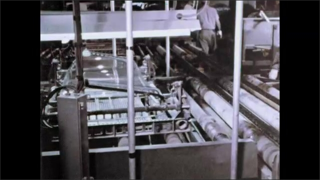 1960s: Sheet of glass on large carriage moves down conveyor belt in automotive factory. Two men remove sheet of glass and stack it.