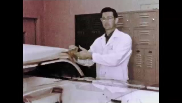 1960s: Windshields move down conveyor belt in automotive factory as workers cover them for safety.