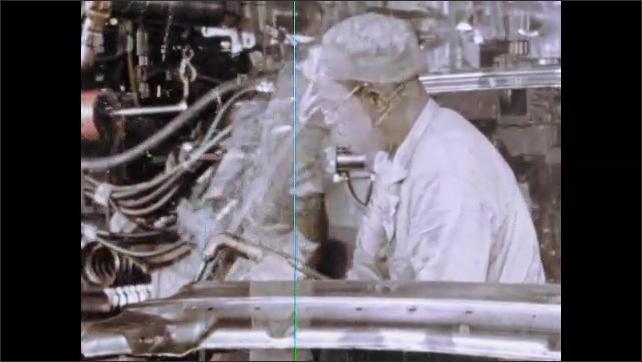1960s: Man welding car parts. Machine lifts frame of car, man guides car.