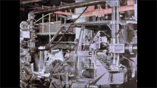 1960s: Hand moves machine part. Man welding metal part. Workers assembling frame of car. Machine lifts frame of car.