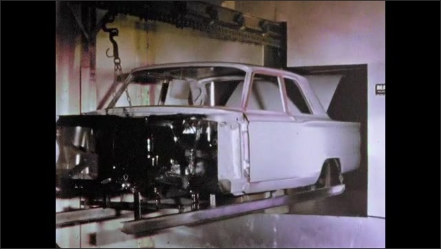 1960s: Machine moves car frame in factory. Man buffing side of car.