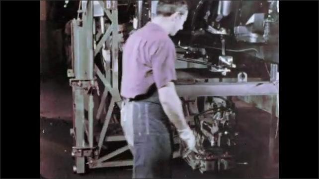 1960s: Pan across cars in parking lot. Men lift machinery in factory.