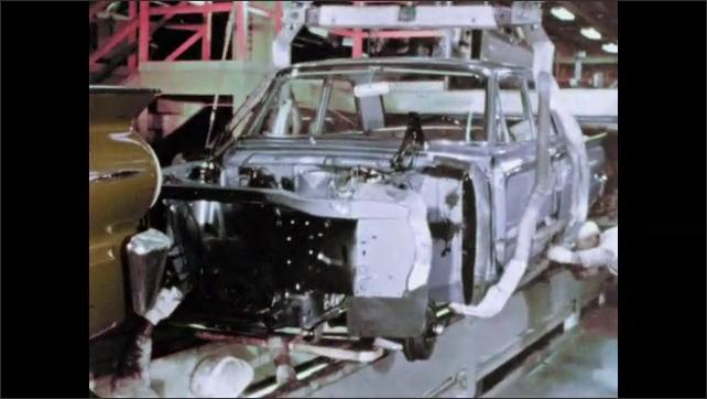 1960s: Machine lowers car frame onto assembly line.
