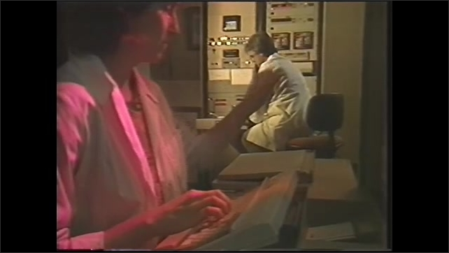 1990s: Man and woman work in control room.  People press buttons.  Surface of moon.