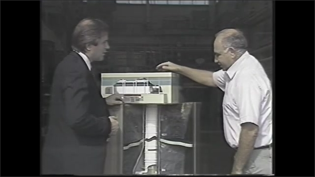 1990s: Men work in control room.  Men talk and look at scale model.