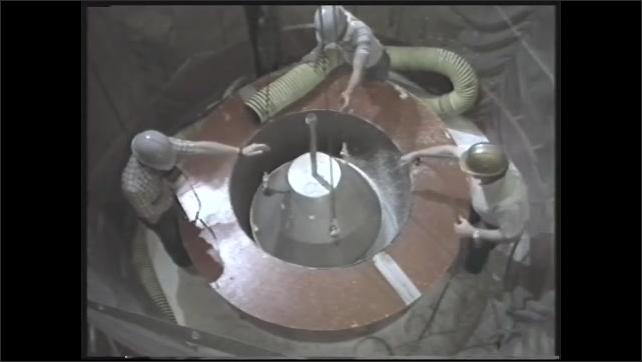 1990s: Metal object falls into tube.  White pellets fly.  Men retrieve pod from tunnel.  Tower.