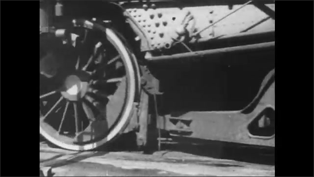 1940s: Pistons pump and wheels of locomotive engine move on track. Model train runs along circular toy track.