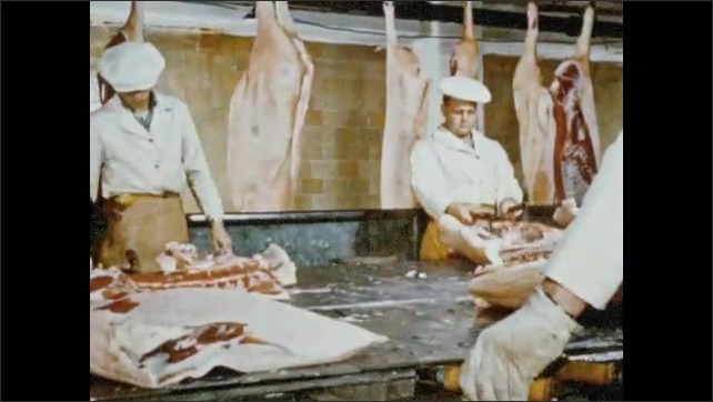 1950s: Man moves side of beef through refrigerated warehouse. Workers remove loin with large knife. Man operates meat canning machine. Man operates sausage vat. Woman ties off sausages.