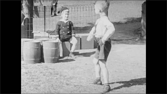 1940s: UNITED STATES: boy hangs upside down on bar. Boys play outdoors. Boy takes food.