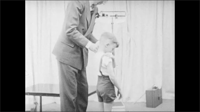 1940s: UNITED STATES: Children's Records. Originals and File Copies. Filing cabinet label. Man sorts out child's braces. Boy talks to man.