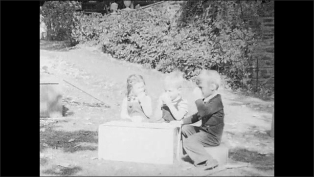 1940s: UNITED STATES: lady and children in garden. Children sit at block. Lady gives drinks to children