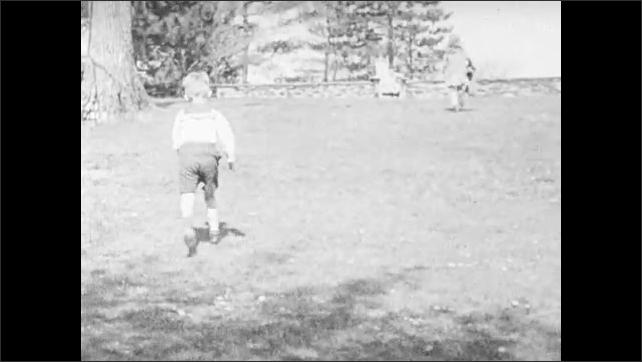 1940s: UNITED STATES: children play outside house. Children race in garden. Slow motion of children running
