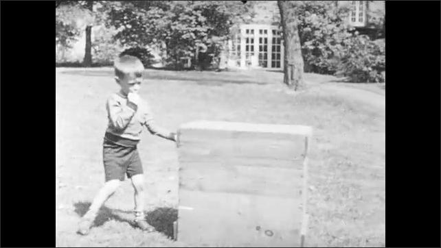 1940s: UNITED STATES: children race in garden. Boy pushes box in garden.