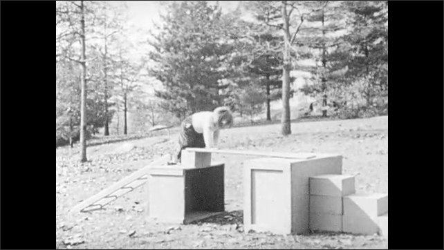 1940s: Boy climbs across playground obstacle.