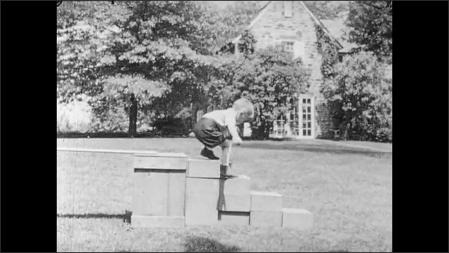 "1940s: Caption reads ""Robert.  Age 4.""  Boy walks across playground obstacle.  Boy hands object to teacher.  Boy runs to woman."