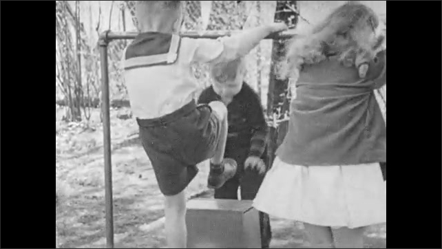 """1940s: Caption reads """"Robert.  Age 5.""""  Little boy attempts to hang from bar with classmates.  Boy brings box.  Boy uses box to get to bar."""