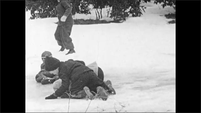 1940s: Boy runs.  Children play in snow.  Boy falls onto child.