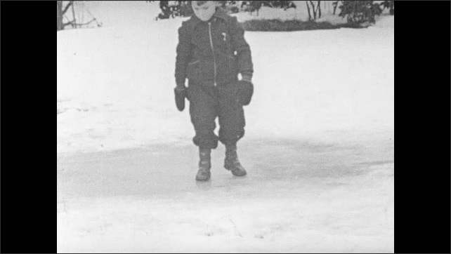 1940s: Boy stands on patch of ice.  Child runs and slips on ice.