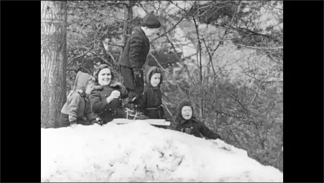 1940s: Boy tries to slide down hill on wooden skis.  Teacher pushes boy.  Children watch.  Boy falls and cries.