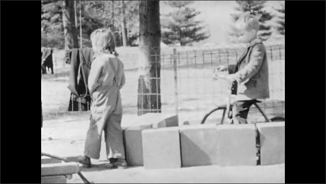 1940s: Children play.  Boys move wagons and wheelbarrows.