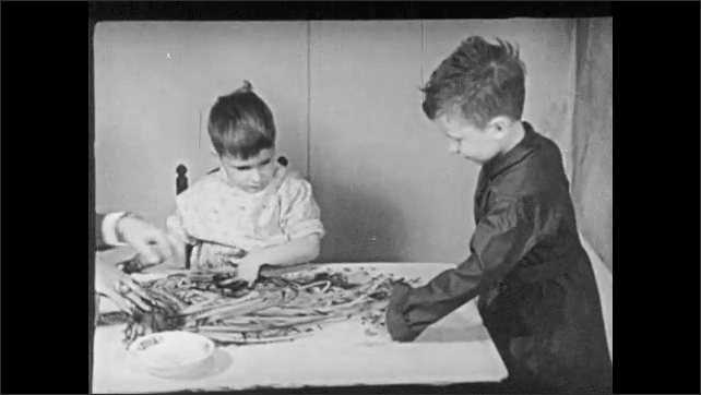 """1940s: Woman bends to demonstrate fingerpainting to boy. Boy in dark smock watches other boy fingerpaint at table. Intertitle """"Robert 4 1/2"""". Boy sits at table with paint."""