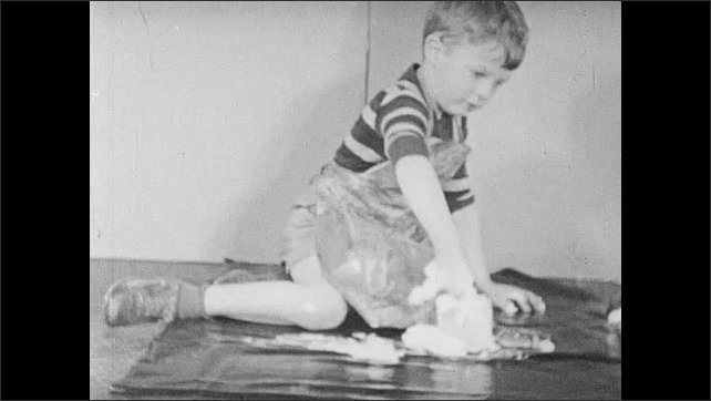 1940s: Boy empties gobs of paint from jar onto plastic sheet. Boy begins spreading paint on sheet with hands.