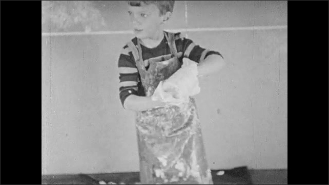 1940s: Boy in apron holds jar of paint and lid. Boy tilts the jar on its side and upside down. Paint drops on plastic sheet and boy smears paint with his feet.
