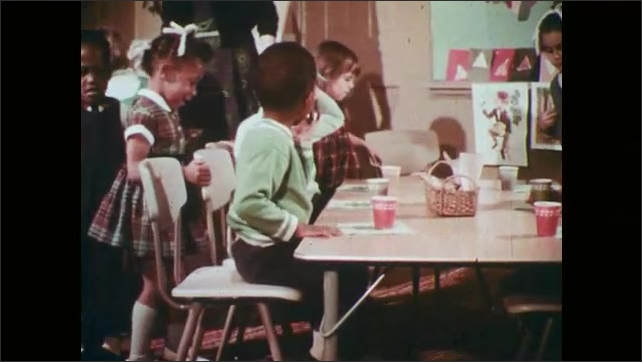 1970s: Classroom.  Children enter and sit at tables.  Boy drinks.