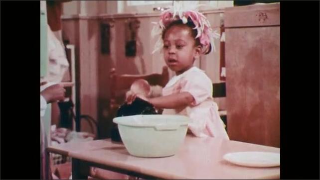 1970s: Classroom.  Little girls talk on telephone and bead bracelets.