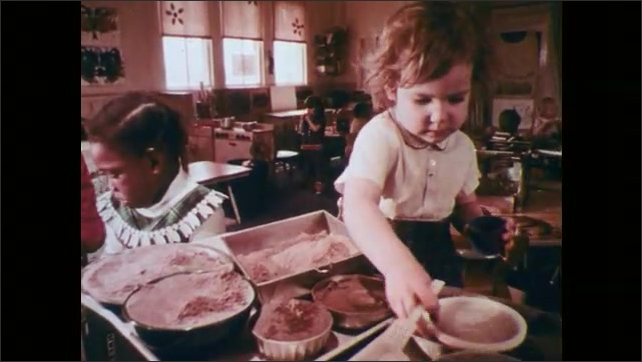 1970s: Young girl partitions flour into different bowls, in classroom.
