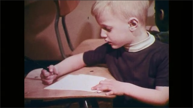 1970s: Hand holding pencil draws circles. Boy seated at classroom table is drawing circles with pencil, on sheet of paper.