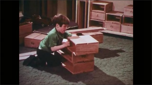 1970s: Boy in classroom stacks wood boxes and places wood boards over the top of them.