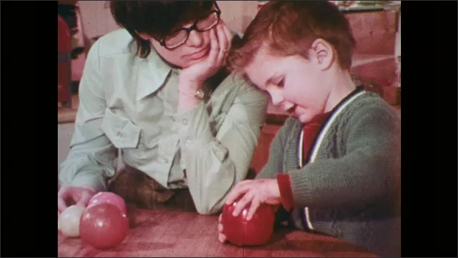 1970s: Children listening to woman read book to them. Woman reads book to children seated around her. Woman shows boy how to open ball, in which smaller ball is inside.