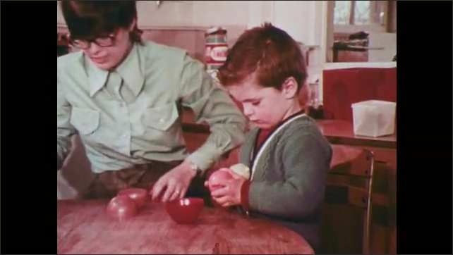 1970s: Woman sits at table with boy as he opens balls and places objects inside.