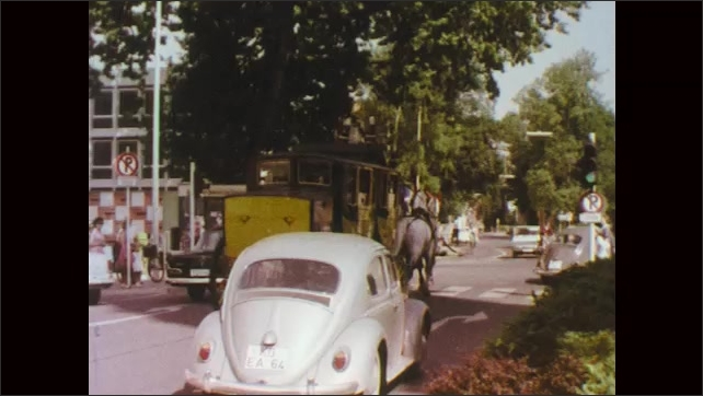 1970s: Person pushes cart on railway. Finger points to map. Vehicles on road. people in coach drawn by horses