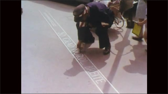1970s:  Buildings and signs on street. Man cleans sign on floor. Numbers on map