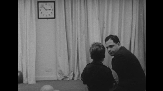 1950s: Boy plays with balloon in room with balloons on floor. Man talks to boy as boy plays with balloon.