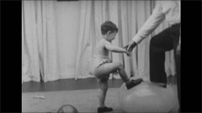 1950s: Boy picks up balloon and throws it. Boy approaches man holding down larger balloon. Man steps on balloon with boy and it pops. Man and boy pop smaller balloon in hands. Man holds balloon.