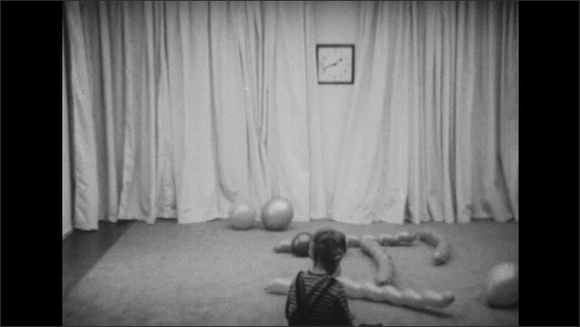 1950s: Boy sits on floor with balloons in observation room. Boy sits on floor and speaks. Man sits in chair near boy on floor and plays with balloon.