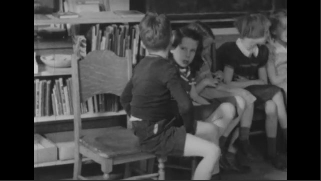 1950s: Students it in semicircle on chairs in classroom. Students sing.