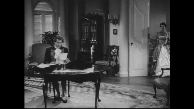 1940s: Man sits at table and reads.  Woman and man enter room.